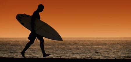 Silhouettes surfer walking on the beach at sunset Imagens - 88932409