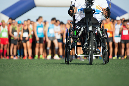 Wheelchair athlete in action during a marathon in the background runners ready to start marathon