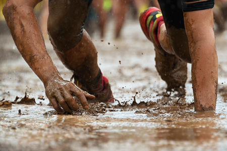Mud race runners.Crawling,passing under a barbed wire obstacles during extreme obstacle race 스톡 콘텐츠