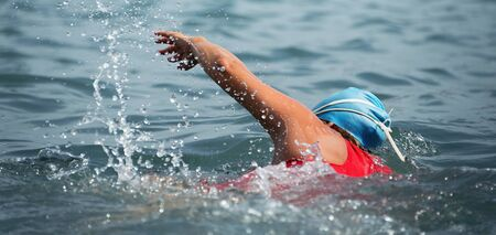 Woman swimmer swimming crawl in blue sea,training for triathlon Stock fotó