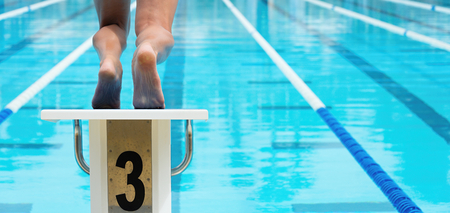 The swimmer jumps from the start block at the start of the race Stock Photo