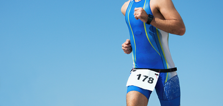Athlete runner running on triathlon race on sunny days