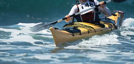 Paddlers race their ocean kayak surf skis through breaking waves