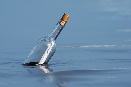 Message in a bottle floating on sea level