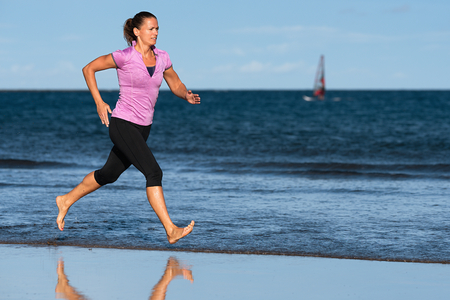 Active sporty woman run running on the beach sun and blue sky, water splashes with her legs