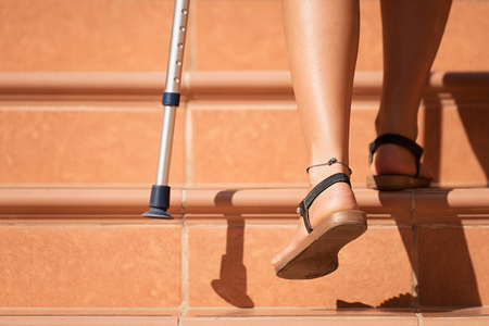 Injured woman trying to walk on crutches on stairs