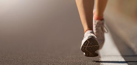 Hardloopschoen close-up van vrouw die op de weg loopt met sportschoenen