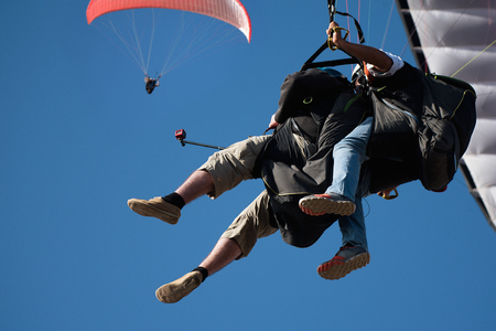 Two paraglider tandem fly against the blue sky,tandem paragliding guided by a pilot Фото со стока