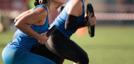 Mud race runners, group of racers squat with a dumbbell Stock Photo