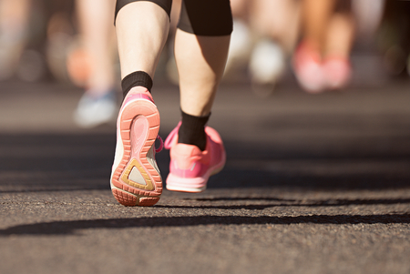 Marathon running in the light of evening on road with sports shoes