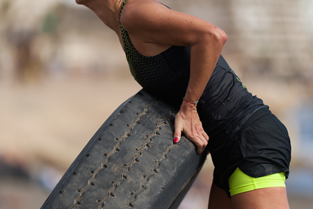 Woman athlete exercising with tire at the outdoors 版權商用圖片