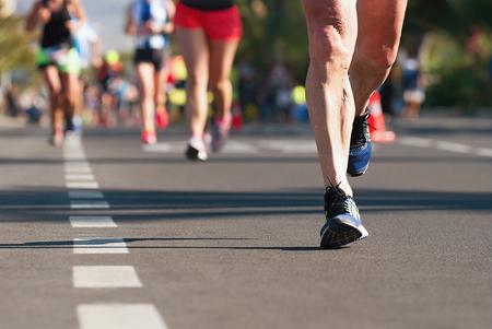 Maratón de carrera, pies de personas en la carretera de la ciudad