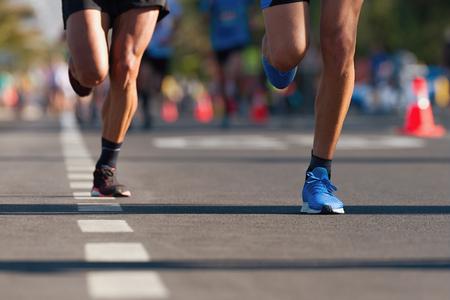 Maratón de carrera, pies de personas en la carretera de la ciudad Foto de archivo