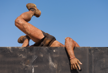 Mud race runners running over obstacles extreme sport Reklamní fotografie