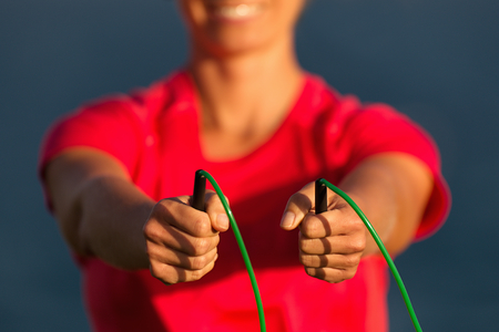 Sports woman holds a skipping rope in his hands is engaged in gymnastics against the background of the sea coast 写真素材