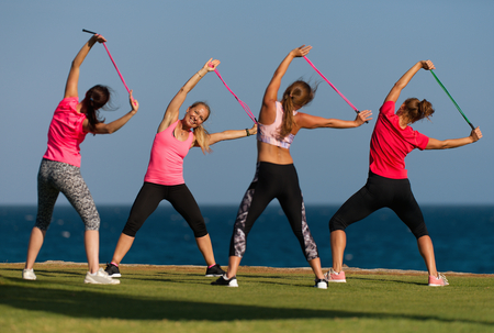 Group of young people doing their fitness training by the sea, using skipping rope Stock Photo