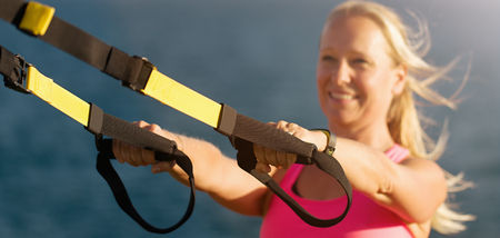 Fitness young woman engaged in morning exercises on the beach during sunrise