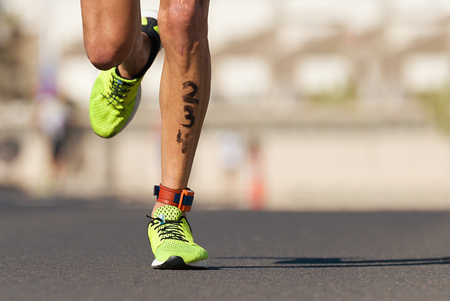 Marathon competition during an ironman the numbers on the leg Stock Photo