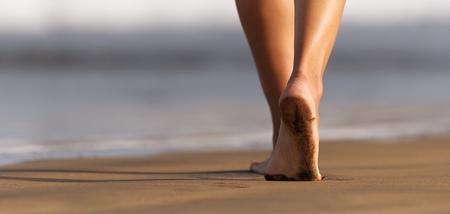 Frauenbeine und -füße gehen auf dem Sand des Strandes mit dem Meerwasser im Hintergrund Standard-Bild
