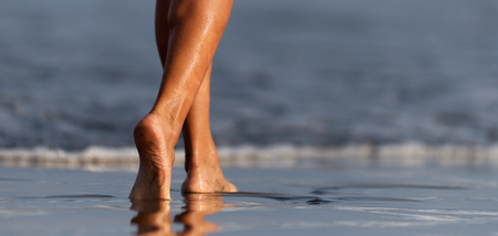 Barefoot woman walking in ocean water waves Reklamní fotografie