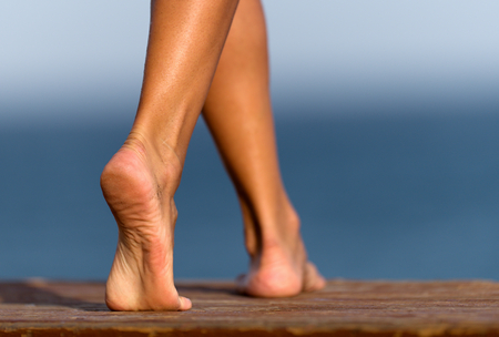 Legs of a woman on a wooden pier on summer, sea and sky background Standard-Bild - 124897956