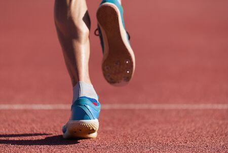 Man runner running on track, close-up on running shoes
