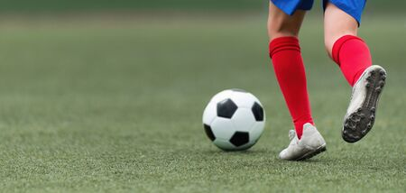 Foot of a child football player and ball on the football field