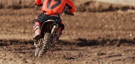 Racer child on motorcycle participates in motocross race, active extreme sport Stok Fotoğraf