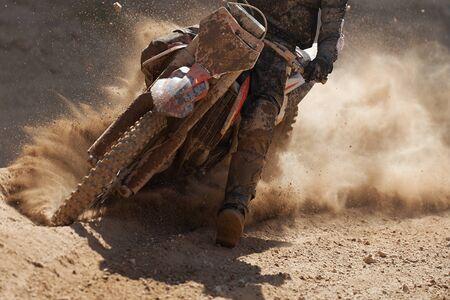 Motocross-Rennfahrer beschleunigt die Geschwindigkeit auf der Strecke und fährt im Motocross-Rennen