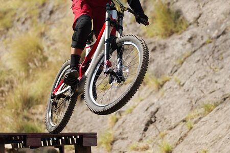 Professional athlete high jumping downhill on the mountain bike cross-country Stok Fotoğraf