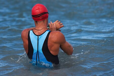 Triathlon swimming sport man start swim time checking, heart rate on smart watch