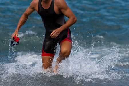 Triathlete swimmer running out of ocean finishing swim race.Fit man ending swimming sprinting determined out of water in professional triathlon suit for ironman