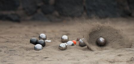 Metallic petanque balls and jack ball on sand