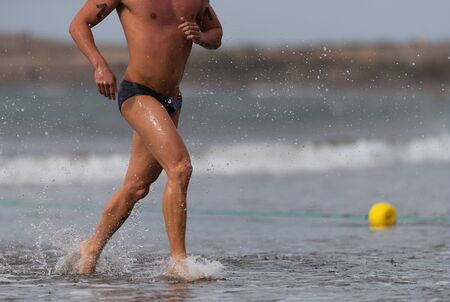 Swimmer running out of ocean finishing swim race.Fit man ending swimming sprinting determined out of water 版權商用圖片