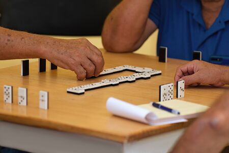 Group of senior people in retirement home playing domino game Reklamní fotografie - 130805702