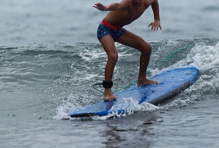 A child learns to surf on the wave,surfing on the blue waves Stok Fotoğraf
