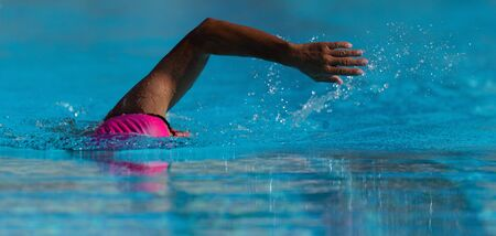 Swim competition swimmer athlete doing crawl stroke in swimming pool