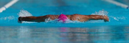 Swim competition swimmer athlete doing butterfly stroke in swimming pool