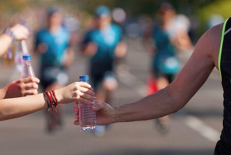 Getränkestation bei einem Laufmarathon, Trinktrinken während eines Rennens