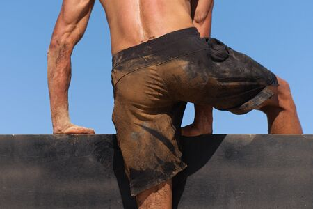 Mud race runners running over obstacles extreme sport