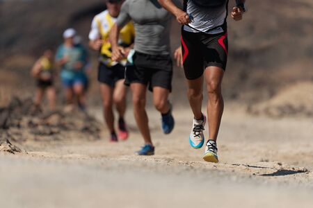 Runners running shoes on trail run. Ultra running athletes legs close up on running in rock path trail Stock Photo