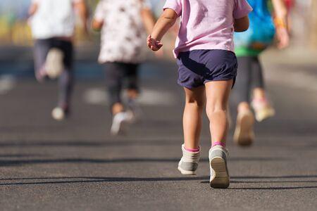 Niños corriendo, atletas jóvenes corren en una carrera para niños, corriendo en el detalle de la carretera de la ciudad en las piernas