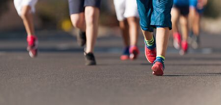 Running children, young athletes run in a kids run race,running on city road detail on legs