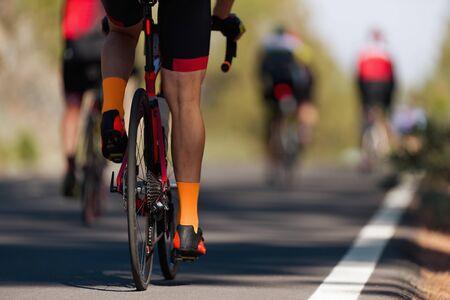 Atleti ciclisti da competizione ciclistica che guidano una gara ad alta velocità, dettagli su ruote dentate e piedi