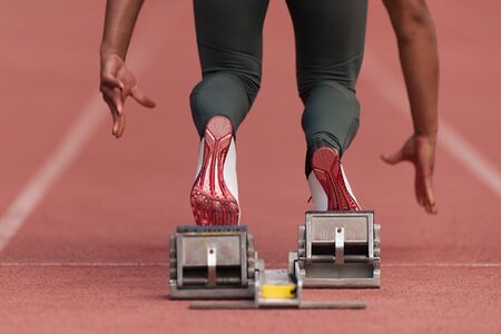 Back view of female feet on starting block ready for a sprint start