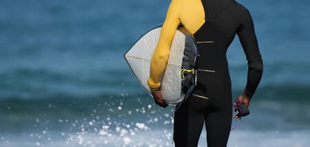 A surfer ready to shore the sea, surfer in a black wetsuit is ready to enter the water