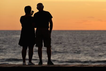Silhouette of an older couple on the ocean coast as they take pictures of the sunset Reklamní fotografie