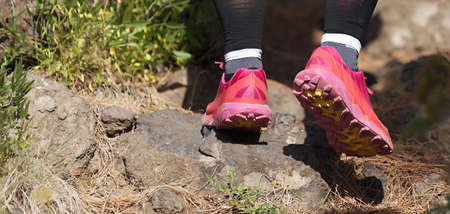 Trail running woman on mountain path exercising