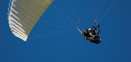 Paraglider tandem fly against the blue sky, tandem paragliding guided by a pilot