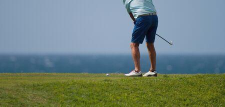 Golfer hitting ball with force. The grass distribution the blur of golf Reklamní fotografie - 143692482
